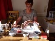 Karin Busche umringt von ihren Arbeitsutensilien